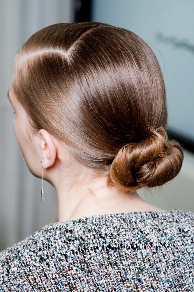 Model with hair pulled back in to a sleek low chignon bun