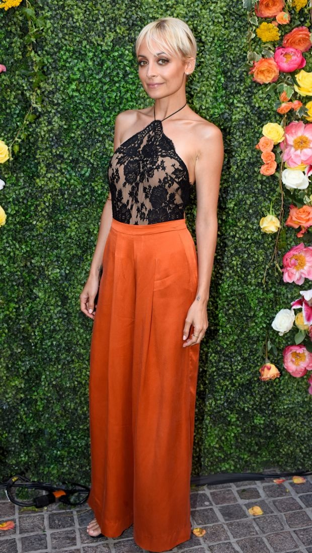 Nicole Richie pairs a black lace halter and orange pants at the Candidly Nicole Season 2 premiere